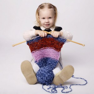 little girl knitting a scarf