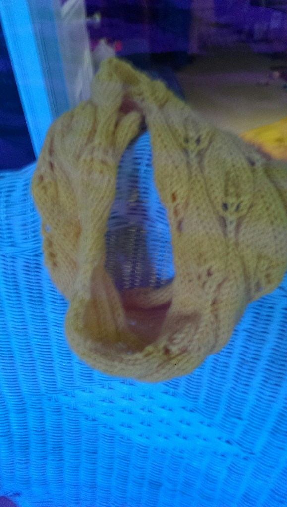 your call cowl pictured on a wicker chair