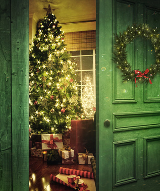 Green colonial door opening into a room filled with Christmas